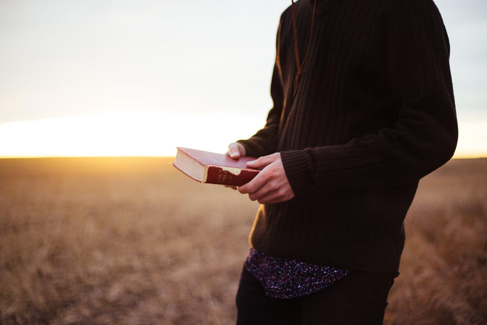 Man holing Bible at sunset