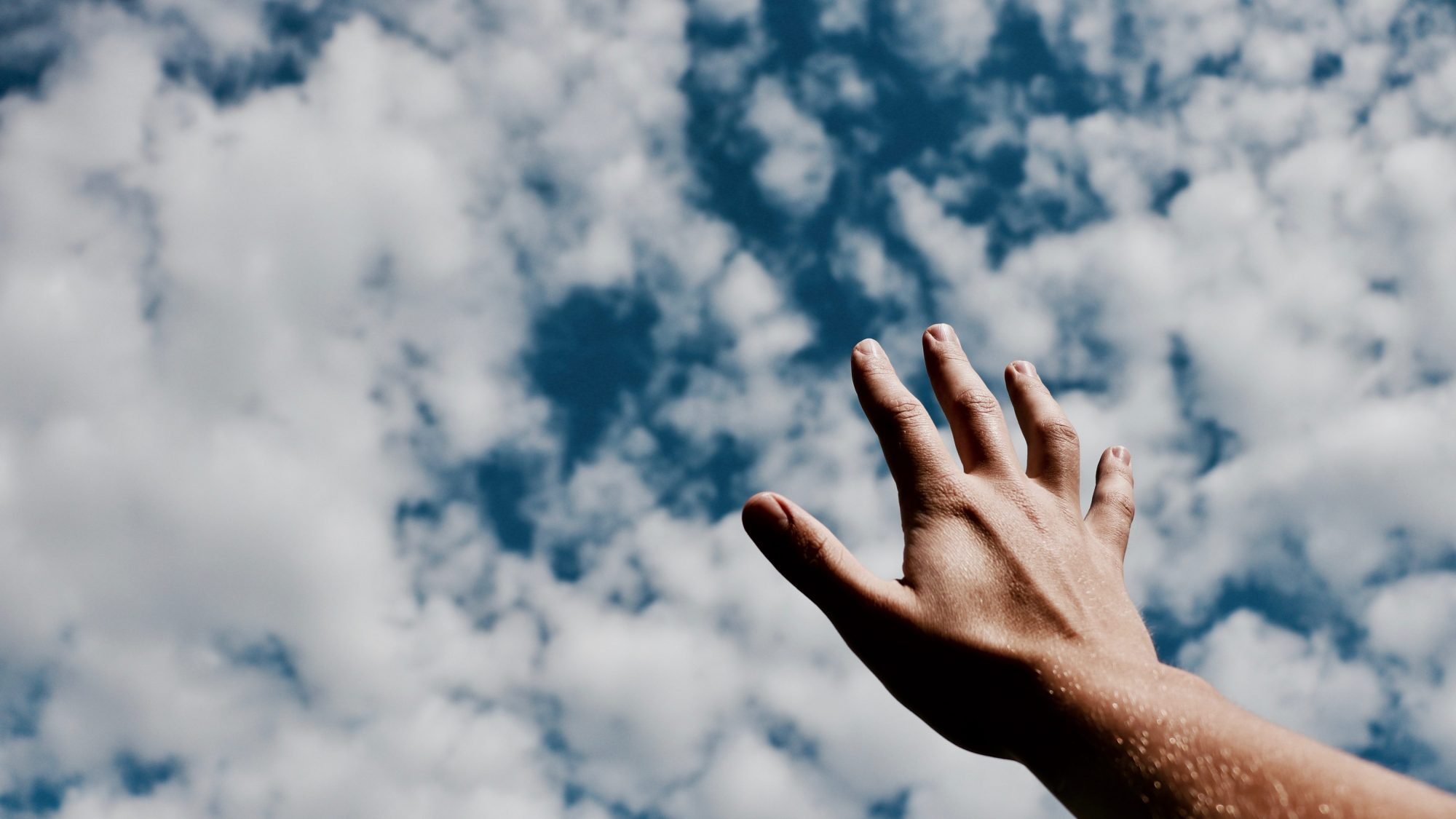 Hand reaching for clouds