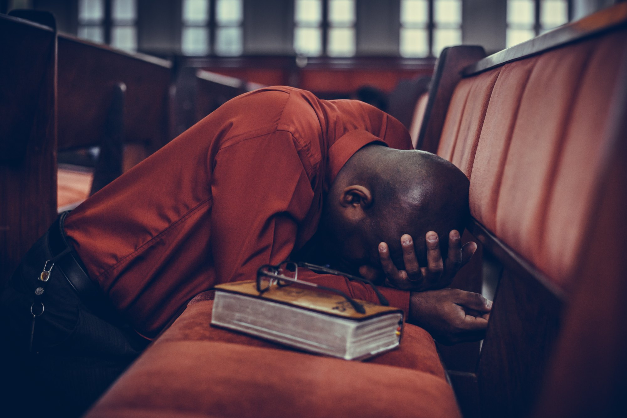 Man praying in church with Bible to represent thinking about the heart of God