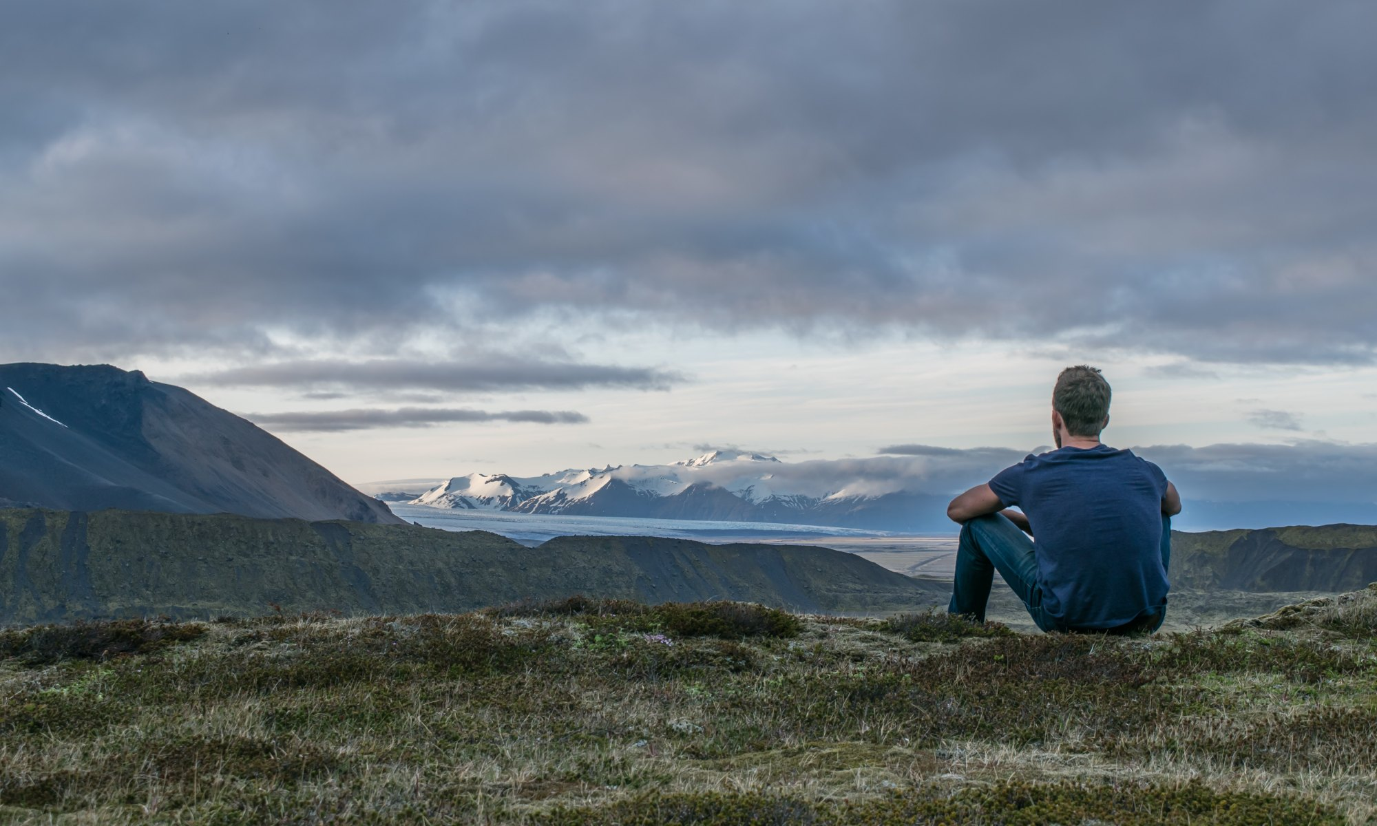 Image of man sitting and looking at mountains to symbolize seeking God and having more faith