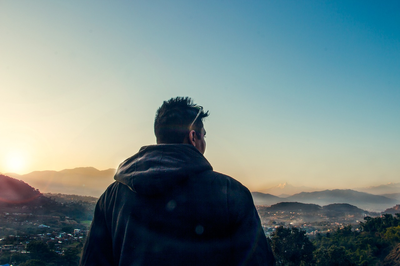 Man looking over horizon to represent making a decision that is difficult and finding help in God.